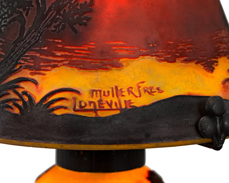 This eye-catching cameo glass lamp from the celebrated Muller Frères glassworks is an exquisite example of the art form. The shade and base are executed in vibrant shades of orange, yellow and terra cotta, which come together to create the