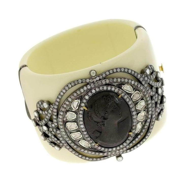This gorgeous grey lava cameo with lady face is all designed with rosecut diamond motif around and put on a ivory color Bakelite cuff which opens from side and sits perfectly on the wrist.   18Kt: 2.89gms Diamond: 9.04Ct Sl: 37.9gms BAKELITE: