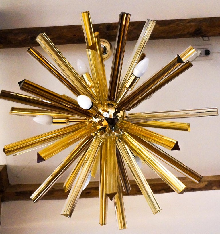 Made up of 41 elements called Trihedrons, this chandelier belongs to that category called sputnik. The amber color of the glass elements perfectly matches the golden color of the frame. It reaches a diameter of 75 cm and, when turned on, it comes