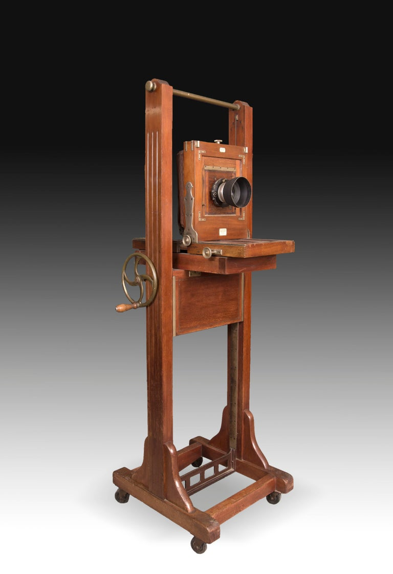 Study camera with bellows in very good condition, two objectives and mounted on easel on casters for professional use that has crank for the adjustment of the camera in height and in diagonals. Made in wood and gold metal and in its color, it