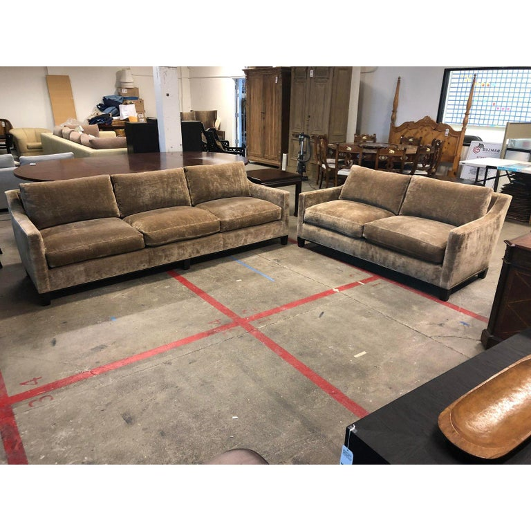 A Lower Park Avenue loveseat and sofa by Cameron collections. This sofa boasts a contemporary Silhouette, with squared arms that gently curve into a slightly angled back. The velvet upholstery is a shimmering wheat color. The wood base is in an