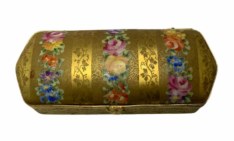 This is a gilded hand painted elongated hinged box. It is decorated with a garland of flowers & festoon of branches of parsley leaves. Inside the lid, there is a single rose hand painted. This is an excellent box to keep jewelry, pen or pencils.