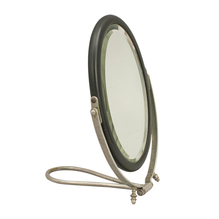 Vintage travellers mirror. A compact campaign mirror in original travelling leather case. The mirror folds up for easy storage and has a plated metal frame with an ebony cased mirror. The folding travellers mirror is ideal for taking on weekend