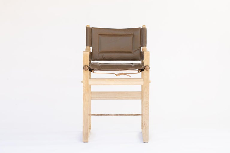 The Safari stool is a testament to Danish midcentury furniture with its simple and gracefully curved frame. Upholstered with a sling seat affixed with sturdy leather straps, the stool is meticulously constructed with traditional joinery and a