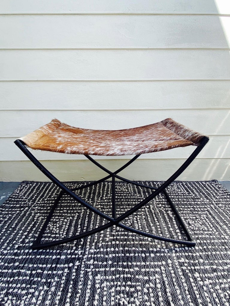 Genuine cowhide leather bench or stool features a handcrafted sling seat with quilted diamond pattern in cognac brown and white. The stool has a Campaign Era design featuring a black wrought iron X- frame with incised grooves and with a center