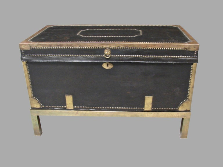 An English campaign style leather and brass mounted trunk, decorated overall with brass banding bordered by nailhead trim, the interior later lined in cut velvet now resting on a custom brass stand of a later date. Possibly of Chinese export origin.