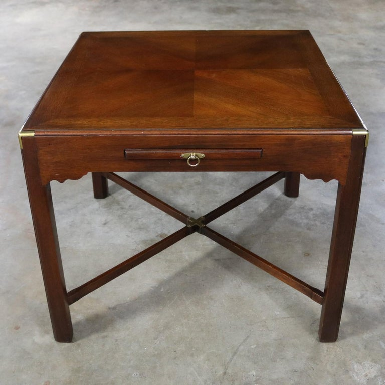 Handsome vintage mahogany Campaign style square side table or end table with a pull-out shelf or tray and beautiful brass accents. This table is in excellent vintage condition, circa midcentury to late 20th century.  This exceptionally beautiful