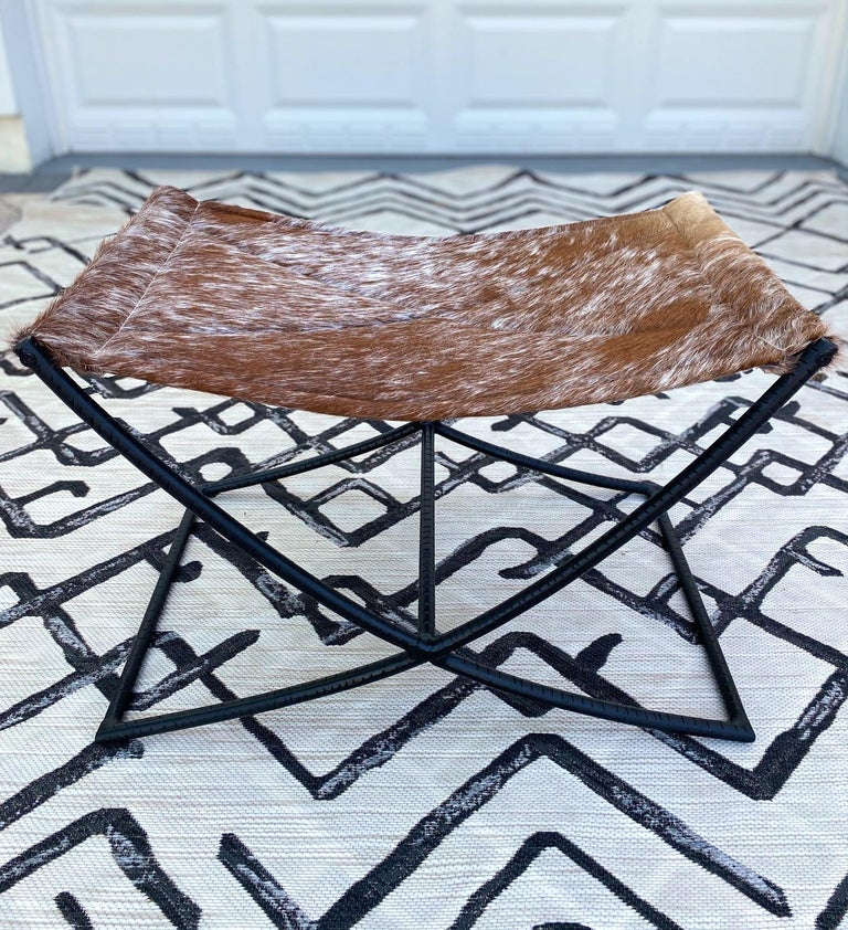 Genuine cowhide leather bench features a handcrafted sling seat with quilted diamond pattern. The stool has a Campaign Era design featuring a black wrought iron X- frame with incised grooves and with a center reinforcement bar. Makes a great accent