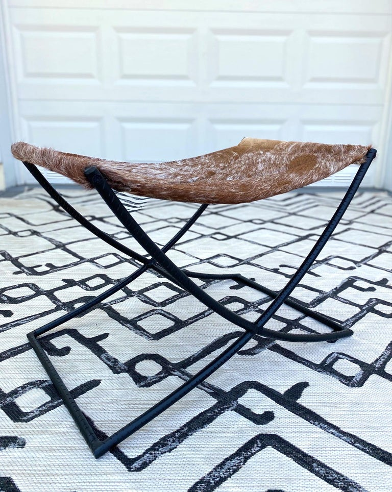 Hand-Crafted Campaign Style Stool with Brown and White Cowhide Seat and Black Iron Base For Sale