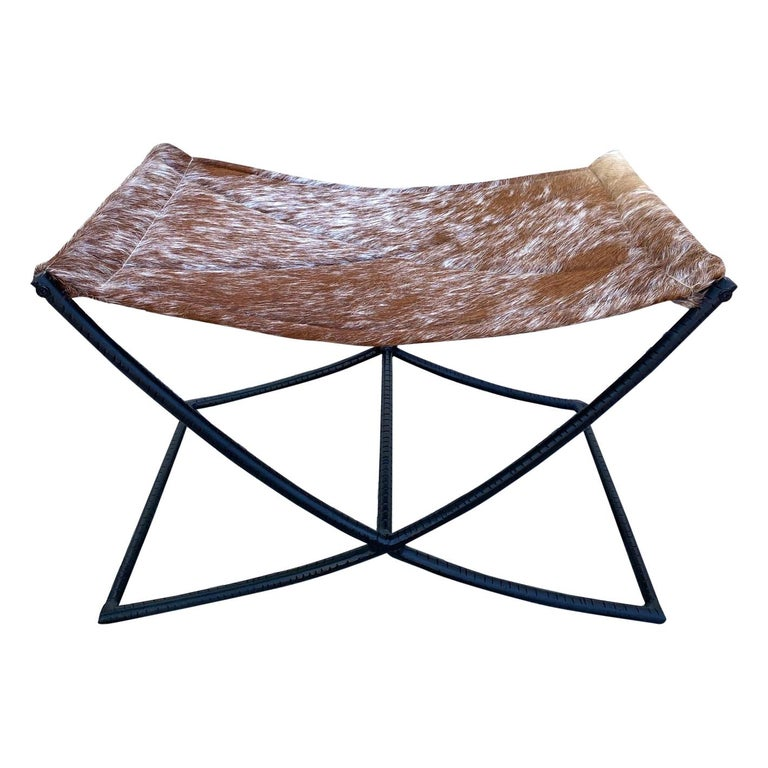 Campaign Style Stool with Brown and White Cowhide Seat and Black Iron Base For Sale