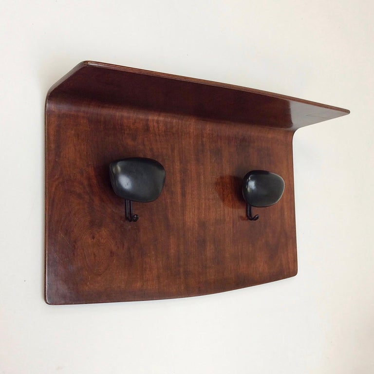 Rare Franco Campo and Carlo Graffi wall-mounted coat rack for Turino Home, circa 1950, Italy. Plywood, metal and black ceramic. Dimensions: 68 cm W, 41 cm H, 24 cm D. All purchases are covered by our Buyer Protection Guarantee.