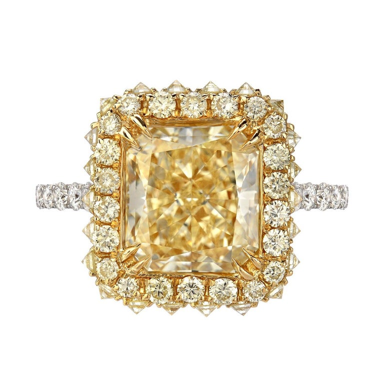 Outstanding 3.78ct Fancy Light Yellow diamond, VS2 clarity, radiant cut, is surrounded by 0.88ct round brilliant Fancy Yellow Diamonds, set inversely on the sides, and 0.66ct G color, VS clarity, round brilliant diamonds set gradually on the