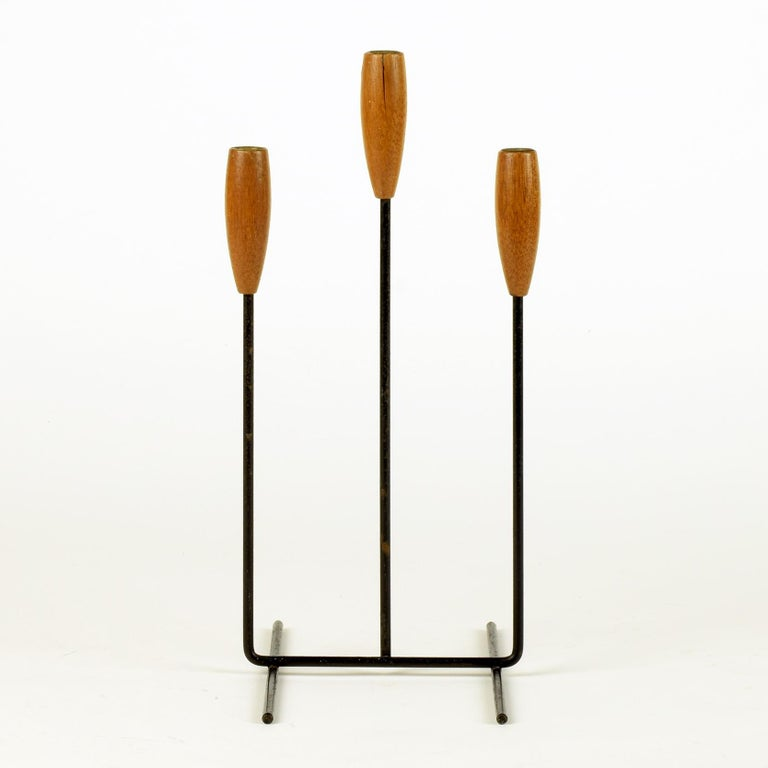 Candleholder for 3 candles, circa 1960  Teak, black metal.  A lovely midcentury item. Overall very good with good age and patina. Slight split in wood to central holder, but this compliments the vintage feel of the piece.