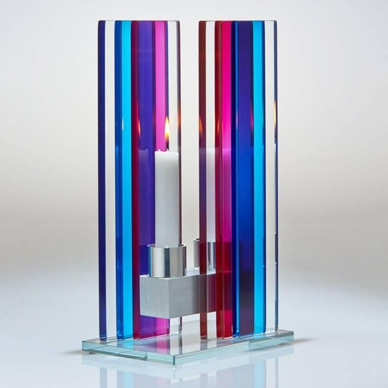 This polished glass, double candle holder is designed by world renowned glass artist, Sidney Hutter. With 40 years of experience in the contemporary glass and Fine art world, Sidney now creates illuminated designs for the home. Create a centerpiece