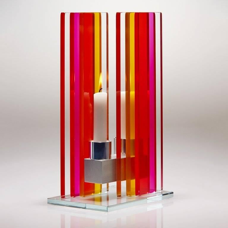 This polished glass, double candleholder is designed by world renowned glass artist, Sidney Hutter. With 40 years of experience in the contemporary glass and fine art world, Sidney now creates illuminated designs for the home. Create a centerpiece