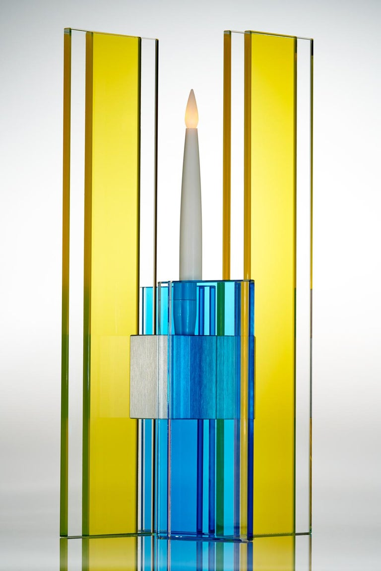 This polished glass candleholder is designed by world renowned glass artist, Sidney Hutter. With 40 years of experience in the contemporary glass and fine art world, Sidney now creates illuminated designs for the home. Create a centerpiece or add