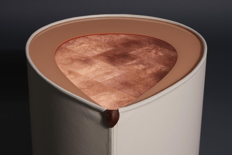 This side table is an exploration into the merging of the unexpected, yet luxurious characteristics of metal leaf and leather. The tabletop consists of a copper leaf and lacquered pattern onto which heavy coats of crystal clear epoxy resin is