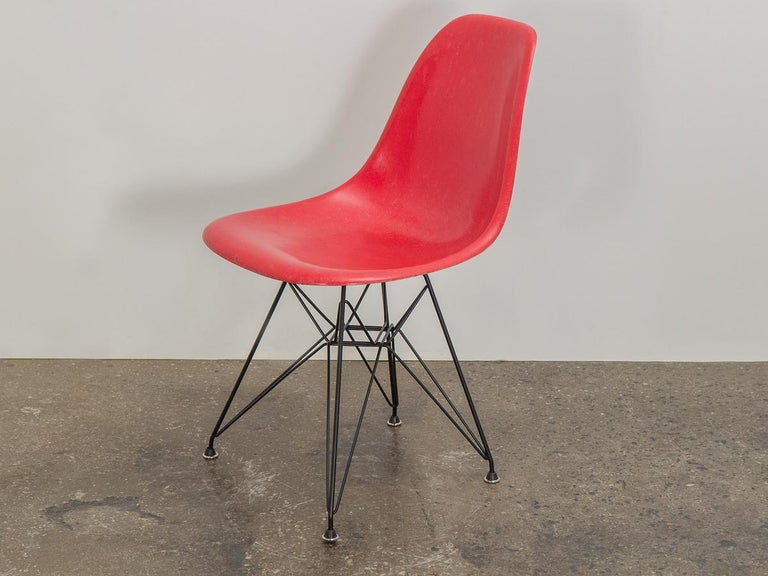 Original 1960s red fiberglass shell side chair designed by Charles and Ray Eames for Herman Miller. The scarce candy red colored shell has its original finish with distinct thread texture. Available as shown — mounted on a new Eiffel base.