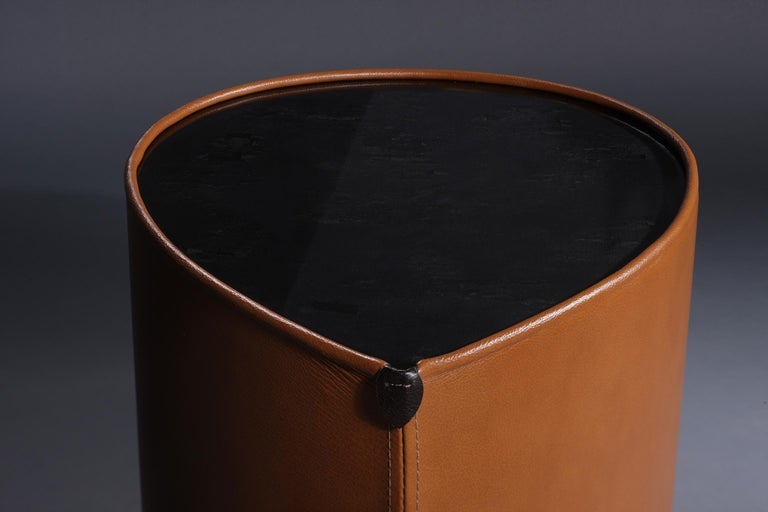 This side table is an exploration into the merging of the unexpected, yet rich characteristics of leather, charred wood and high-gloss resin. The tabletop consists of a charred wood surface onto which heavy coats of crystal clear epoxy resin is