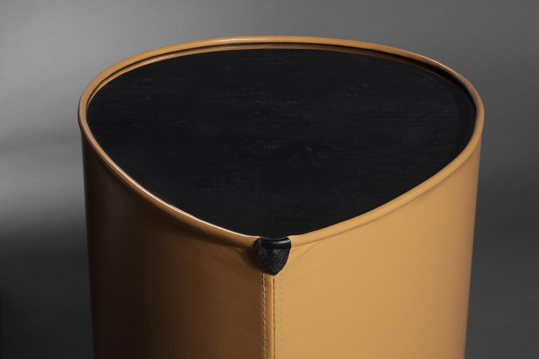 This side table is an exploration into the merging of the unexpected, yet rich characteristics of leather, charred wood and high-gloss resin. The table top consists of a charred wood surface onto which heavy coats of crystal clear epoxy resin is