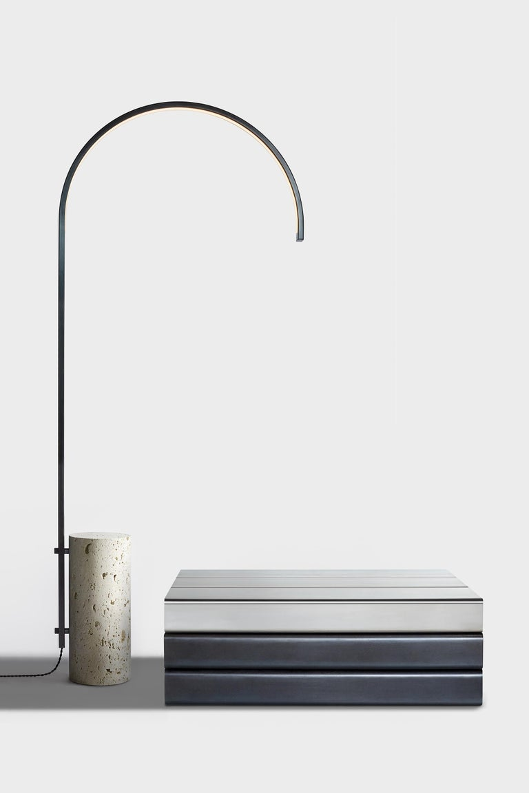The cane floor lamp, the first freestanding light by AlexAllen Studio, carefully balances the physical mass of its limestone base with the light, elegant curve of its illuminated stem.   Available in four finishes: Bronze, mottled brass, gunmetal,