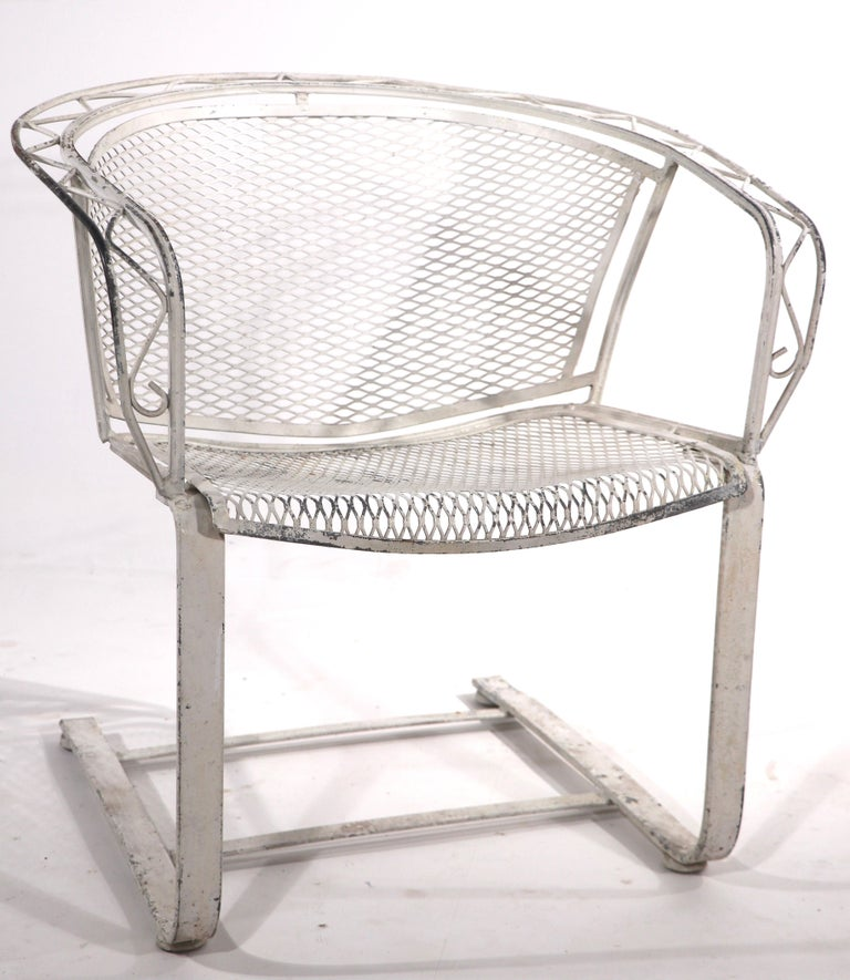 Hard to find cantilevered lounge chair by Salterini. This example has a wrought iron frame with zig zag metalwork trim, and metal mesh seat and back. The chair is in very good original condition, no breaks, bends damage or repairs. The paint finish