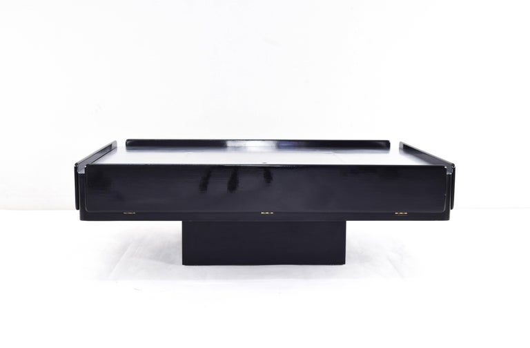Caori coffee or cocktail table. Iconic piece of Italian design. Designed by Vico Magistretti and manufactured by Gavina in Italy in the 1960s. Composed of lacquered beechwood and brushed aluminum top. It has two drawers, two folding front