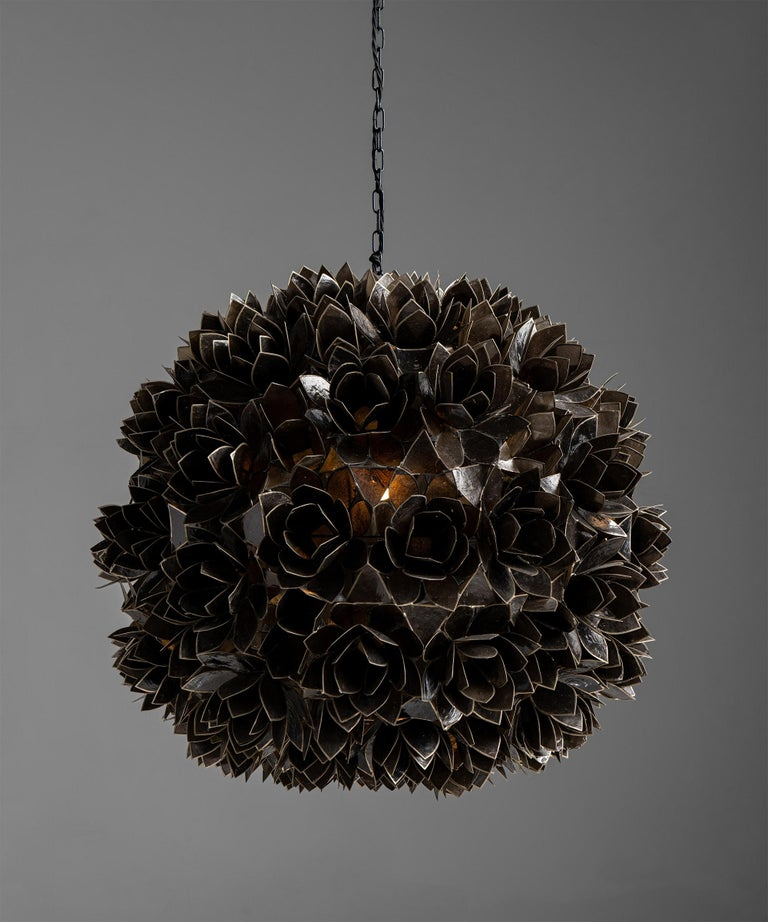 "Capiz shell pendant, France, circa 1960  Black capiz shells with tin armature, forming a series of flowers.  Measures: 24.5"" diameter x 27"" height  $ 7,200."
