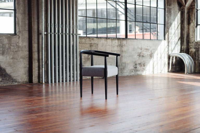 Phloem Studio Captains chair is a modern contemporary take on a classic Captains chair handmade custom to order with turned tapered and shaped legs and a horseshoe shape tube arm and back shaped from solid wood. Appropriate as both a dining chair or