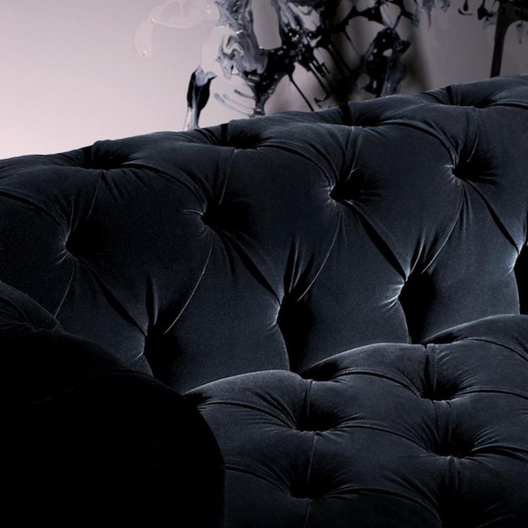 Distinctive for a striking tufted black Cat. 3 fabric upholstery, the result of a traditional technique carried entirely by hand, this elegant sofa is an imposing design that will make a statement in both a traditional and a contemporary interior.