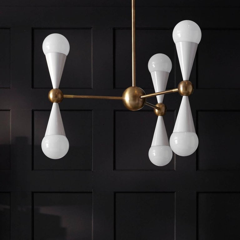 Kinetic modernism. Simple geometric shapes, cones and spheres, collide with dynamic results in our Caracas six-light chandelier. The three arms offer countless configurations, vertical for a Classic vibe, horizontal for a more streamlined look, or