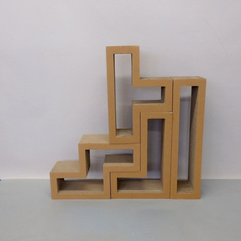 Four pieces of corrugated cardboard that fit together in a variety of ways. Entry way console shelf to coffee cocktail table. Attributed to architect Frank Gehry.
