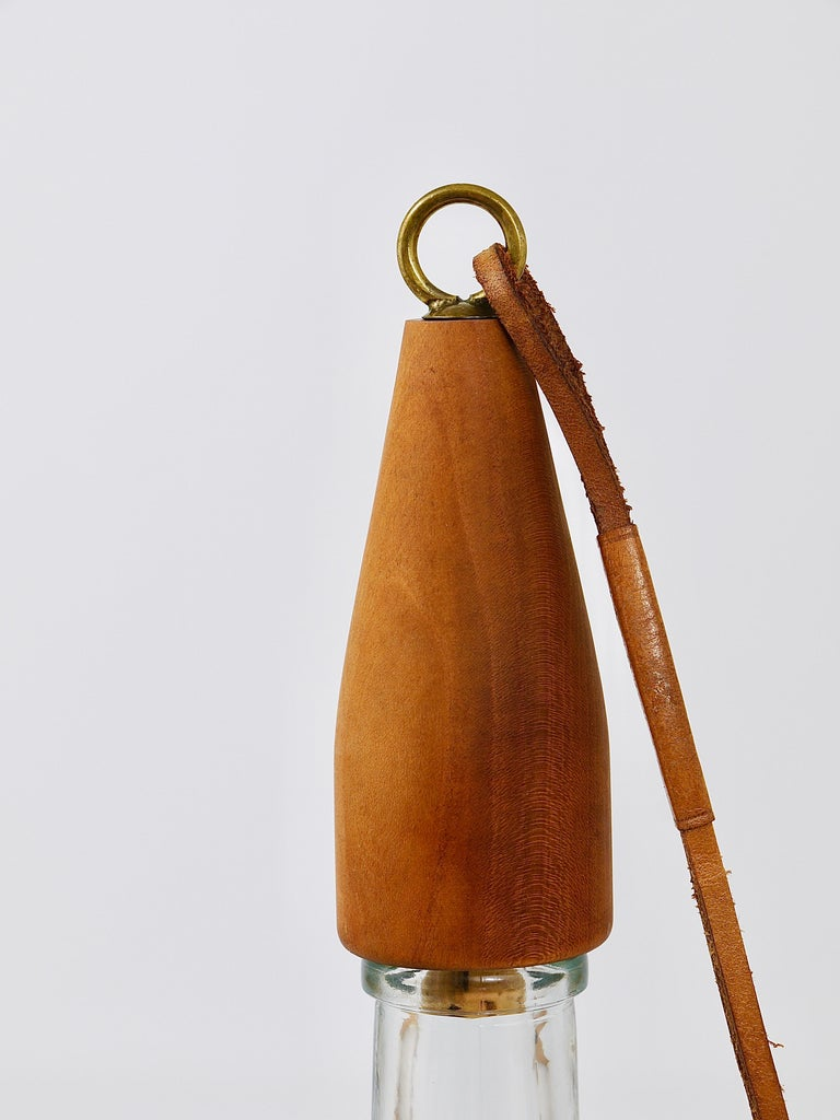 A beautiful Austrian modernist bottle stopper, made of walnut and brass and the original leather string, designed and executed in the 1950s by Carl Auböck, Vienna. In very good condition.