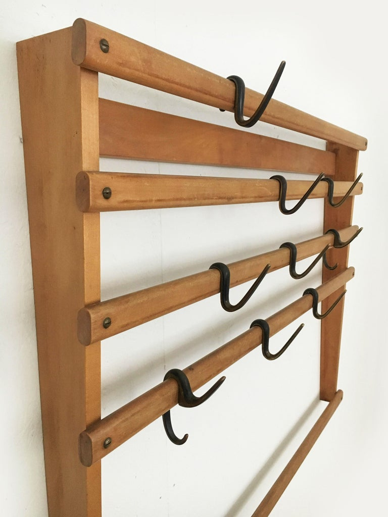 Beautiful rare wall-mounted coat rack wardrobe by Carl Auböck. The two 'G'- and seven 's'-shaped hooks are cast brass and finished combining two surface treatments. They are black patinated and polished on their sides. In excellent vintage condition