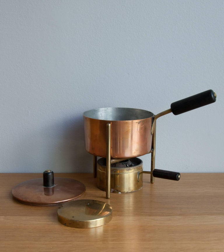Vintage fondue pot and burner by Carl Auböck II, Vienna, circa 1950. The pot and its lid are made out of formed tinned copper, while the burner is in formed brass. The pot, its lid and the burner, all have brass handles covered in ebonized wood. A