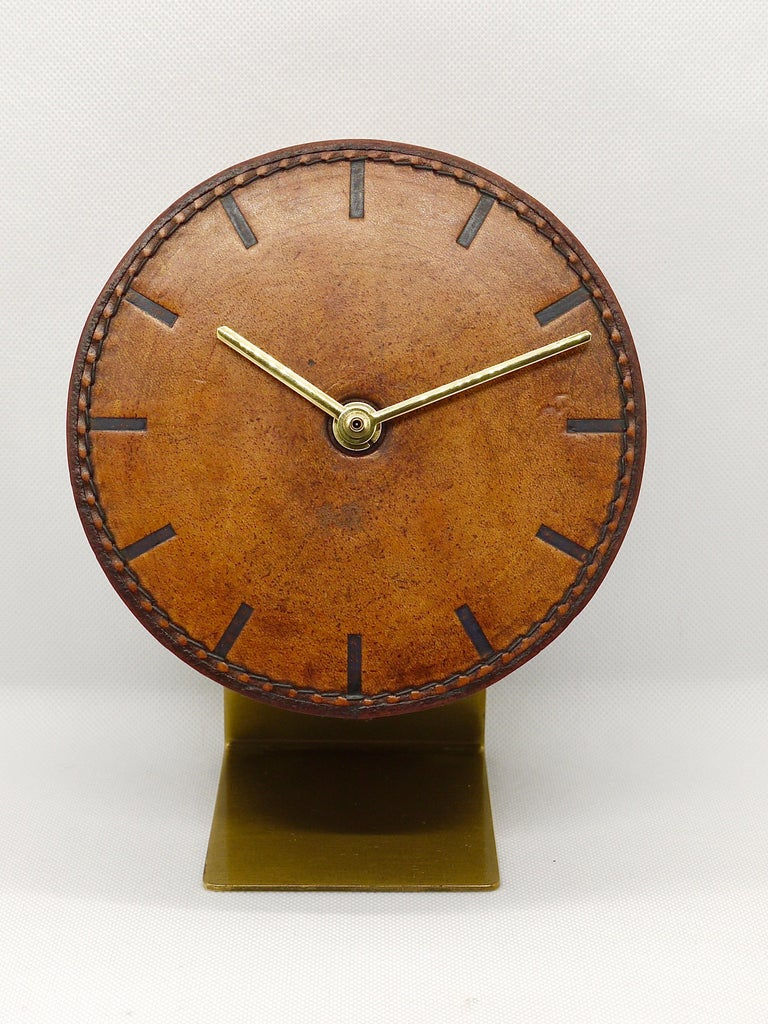A beautiful leather and brass modernist clock from the 1950s, designed and executed by Carl Auböck, Vienna/Austria. An amazing straight-lined clock, has a leather covered clocks face and embossed marks for each hour. Battery-operated movement. Very