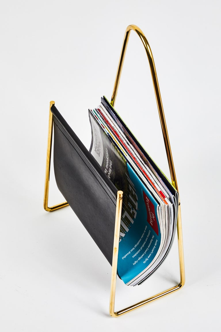 Carl Auböck model #3642 brass and leather table designed in the 1950s, this incredibly refined and sculptural magazine rack is executed in beautifully grained black cowhide leather and polished brass.  Price is per item.   Produced by Carl Auböck