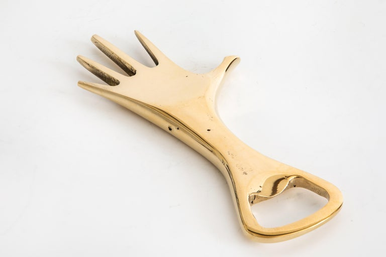 CarlAuböck Model #4224 'Hand' brass bottle opener. Designed in the 1950s, this incredibly refined and sculptural bottle opener is executed in polished brass.   Price is per item. Three in stock ready to ship. Available in unlimited quantities.
