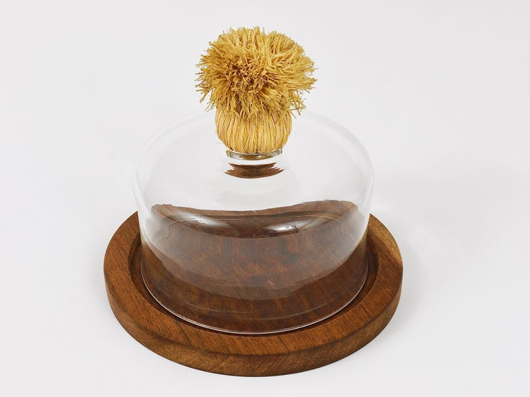 A beautiful midcentury walnut cheese board with a glass dome and a raffia handle from the 1950s. Designed and executed by Carl Auböck. The total diameter is 8 inches, the glass dome has a diameter of 6 inches and a height of 3 1/2 inches without the