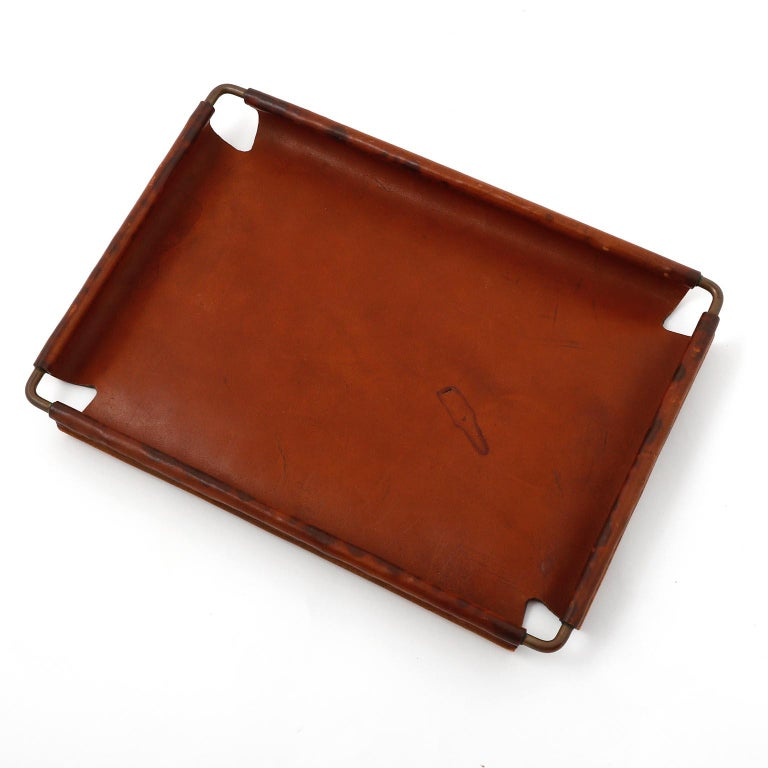 A leather and brass tray designed by Carl Auböck, manufactured by Carl Auböck workshop in midcentury, circa 1950. The aged brass and leather show signs of wear and use. An authentic handmade piece with nice patina on brass and leather. This tray