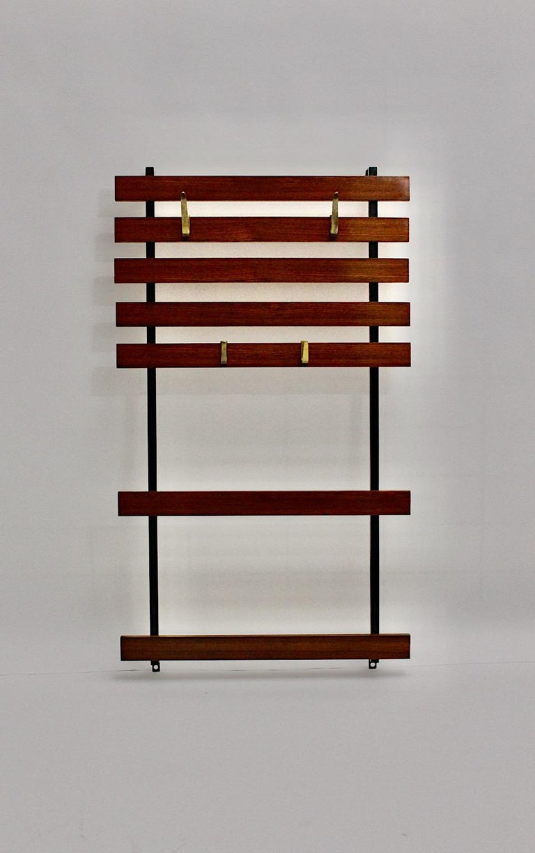 Mid-Century Modern vintage walnut coat rack with 4 cast solid brass hooks, which was designed and manufactured in Vienna, Austria. The black lacquered metal frame shows 7 hardwood stained slats, which is provided for wall mounting, while the 4 cast