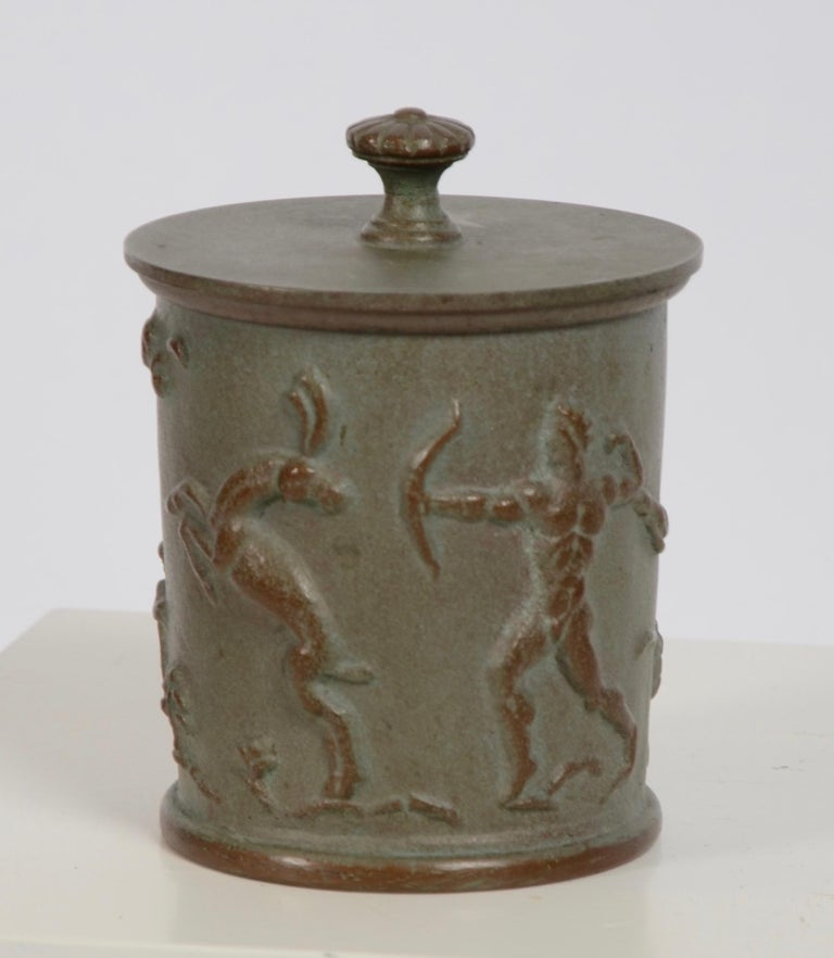 A Swedish Grace cast iron tobacco jar with relief hunting scenery. Designed by Carl Elmberg for Näfveqvarns Bruk, 1920s.