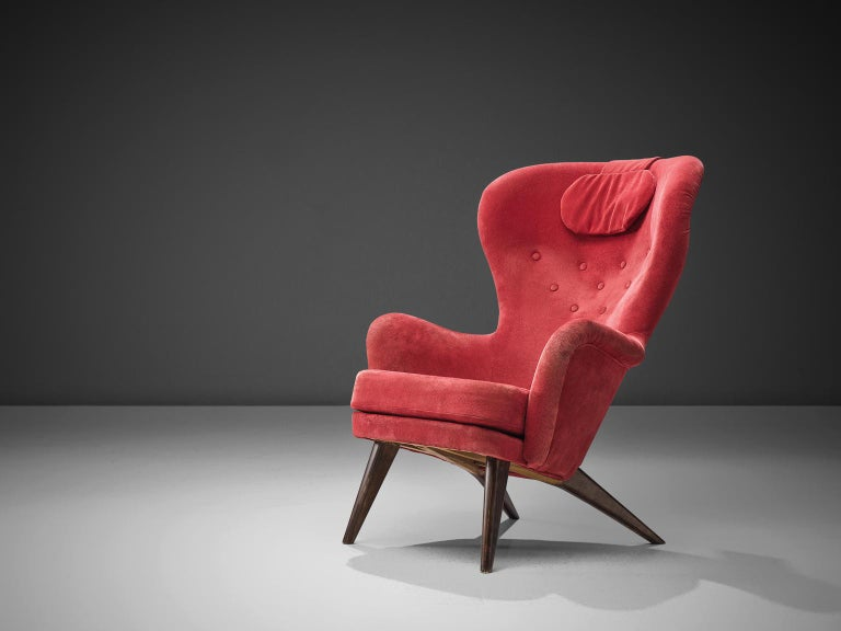 Carl Gustaf Hiort for Puunveisto Oy - Träsnideri Ab, 'Siesta' lounge chair, red fabric, oak, Finland, design 1952, production later.  This sensuous armchair has a curved, slender seat with a slightly winged back. The chair leans slightly backwards