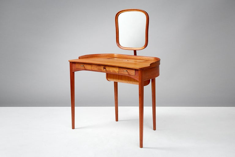 Carl Malmsten  Birgitta dressing table, 1964  Exquisite dressing table produced by Bodafors, Sweden in light mahogany. Adjustable mirror with brass fittings, 3 front drawers with original keys. Additional storage in desk top with tambour door.