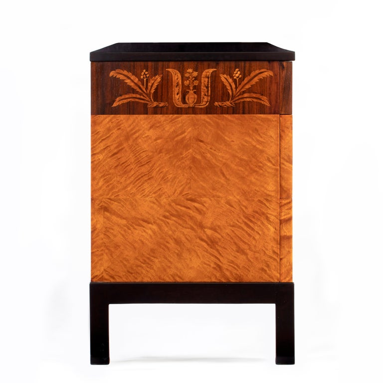 Produced by master cabinetmaker Algot Johansson. Beautifully restored and ready to add to your collection.  The rectangular ebonized birch top, above three stacked drawers, the top drawer depicting a foliate frieze of seared birch and rosewood