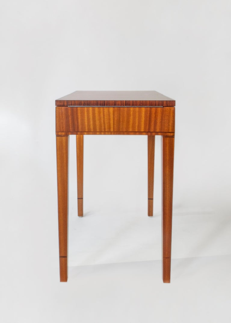 The bookmatched satinwood top, opening on piano hinges to reveal a removable tray divided into fourteen compartments, above a stylized foliate freeze executed in seared holly and boxwood marquetry, on four square tapering legs, with rosewood banding