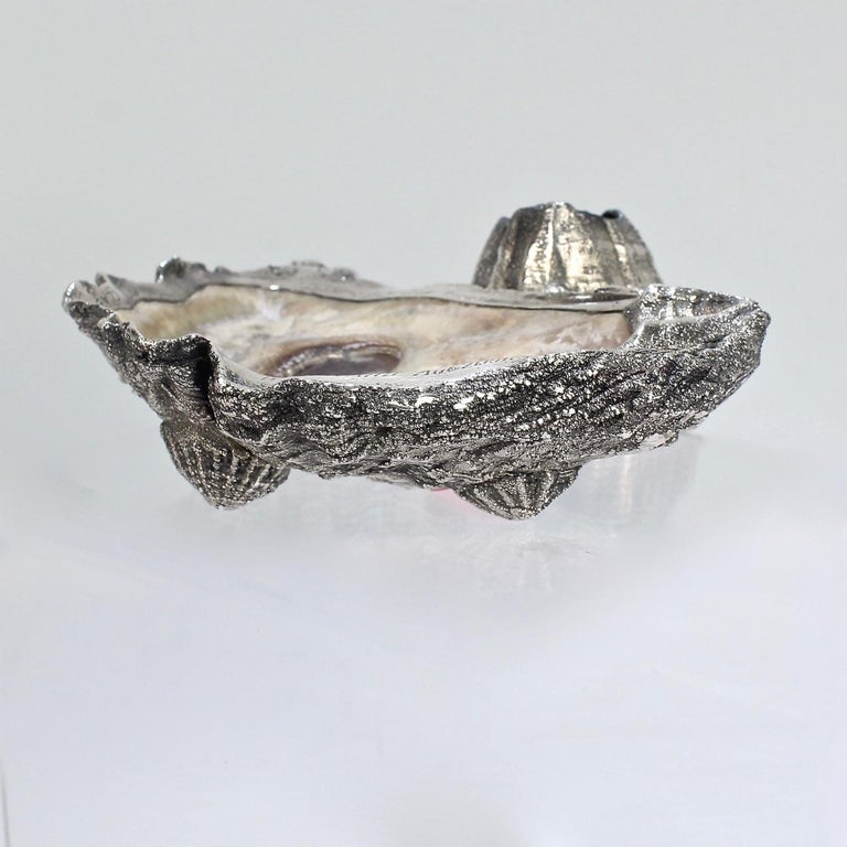 An antique Carl Schon oyster shell & sterling silver ashtray with an integral barnacle match holder and shell feet.  The ashtray is dedicated as yachting trophy for the Atlantic Yacht Club.   (Apparently a winning captain could sometimes chose the