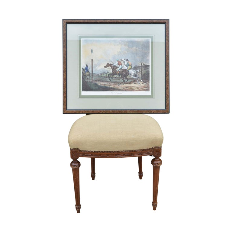 The framed print of Carle Vernet's Le Depart is professionally framed in a faux burled wood look frame and double matted with French rule lines in black and gold. The scene reflects two horses full of energy and their jockeys just out of the gates.
