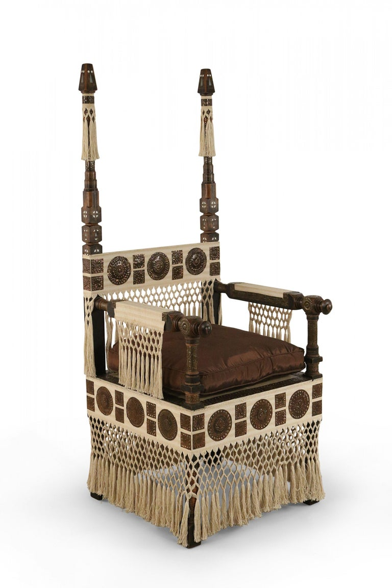 Italian Art Deco mahogany and walnut throne chair with decorative pewter and brass inlay, applied and embossed copper roundels, calfskin vellum seat with brown upholstered seat cushion, and beige fabric detail with woven tassels (Carlo Bugatti).