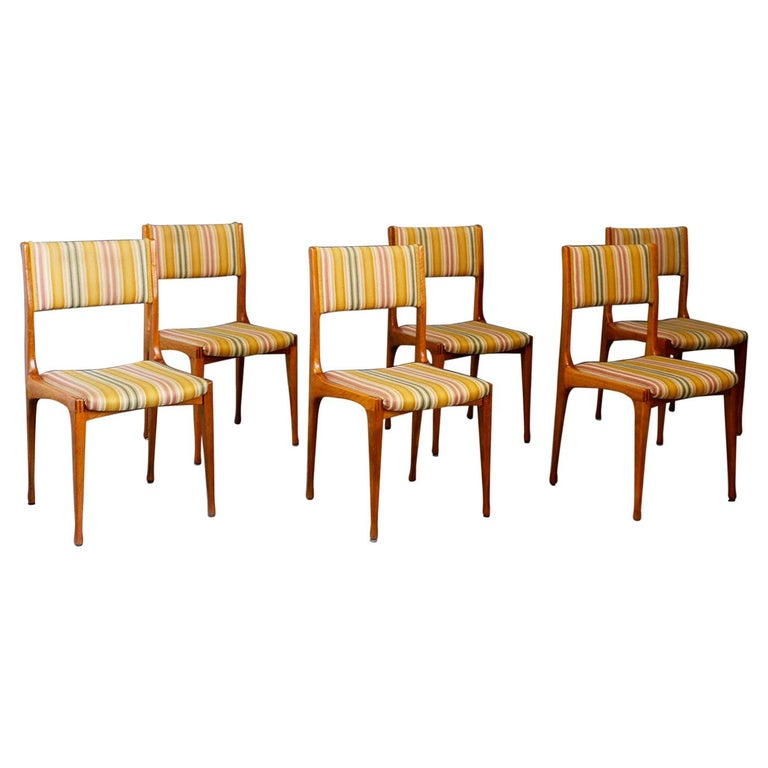 Six chairs designed by Carlo de Carli for the Cassina factory in 1950. The chairs are model 693. They are made with wooden frame and original fabric of the time in excellent condition. The chairs are in excellent condition and are ideal to furnish